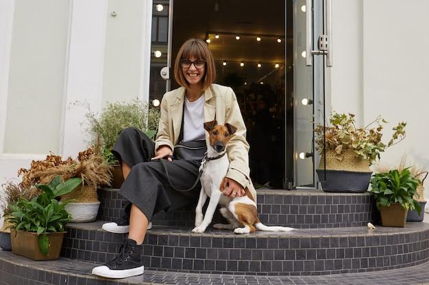 Ritratto di giovane bella signora in occhiali da sole con gioia seduta sulle scale sulla strada della città con il suo piccolo cane carino di razza jack russell terrier