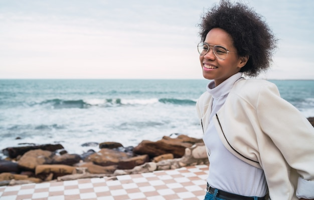 Portrait of young beautiful latin woman enjoying fresh air with the sea on the.