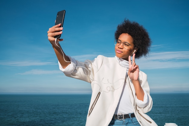 Portrait of young beautiful latin woman taking selfies with her mobile phone outdoors with the sea