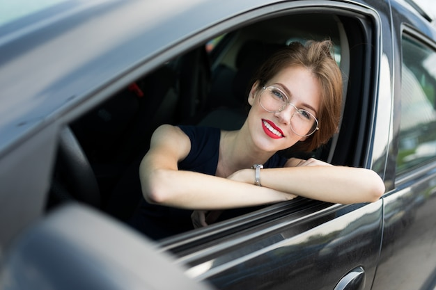 A portrait of young beautiful office woman with bright makeup, red lips sits in a black car