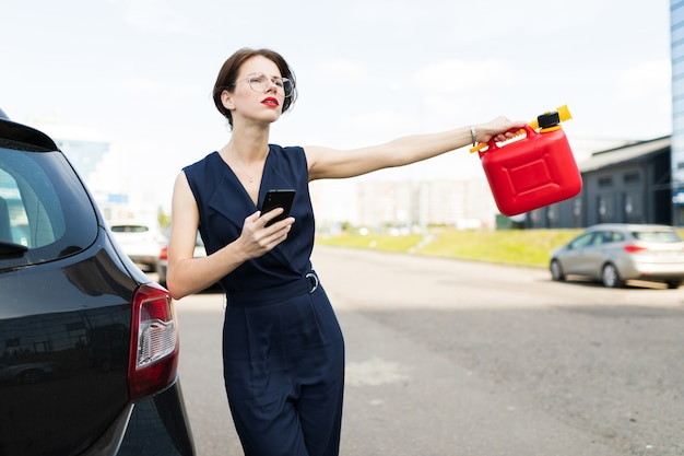 A portrait of young beautiful office woman with bright makeup, red lips stands near a black car and asks for help with petrol