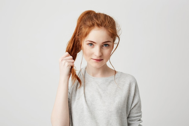 Portrait of young beautiful redhead girl touching her hair tail .
