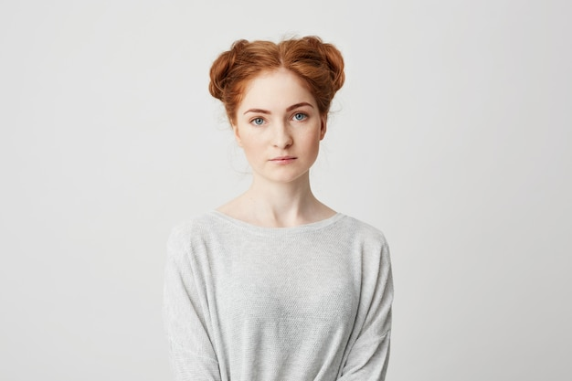 Portrait of young beautiful redhead girl with buns .