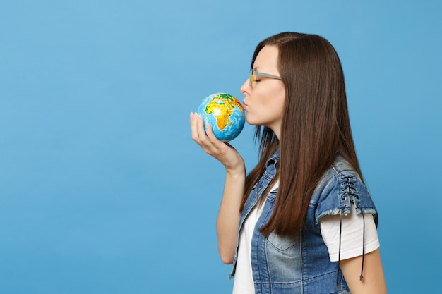 Portrait of young beautiful relaxed calm woman student in glasses holding kissing world globe isolated on blue background. education in university. save planet. ecology environment protection concept.