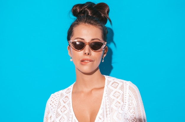 Portrait of young beautiful sexy smiling woman with ghoul hairstyle. trendy girl in casual summer white hipster suit clothes in sunglasses. hot model isolated on blue.biting her lip