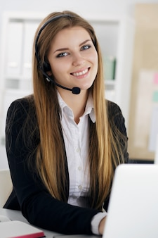 Portrait of young beautiful smiling call center worker talking to someone