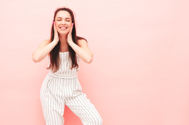 Portrait of young beautiful smiling female in trendy summer hipster overalls clothes
