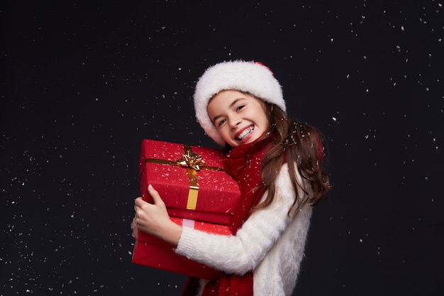 Portrait of young beautiful smiling girl in red santa hat on a dark background