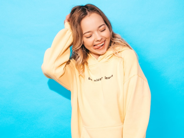 Portrait of young beautiful smiling girl in trendy summer hipster yellow hoodie
