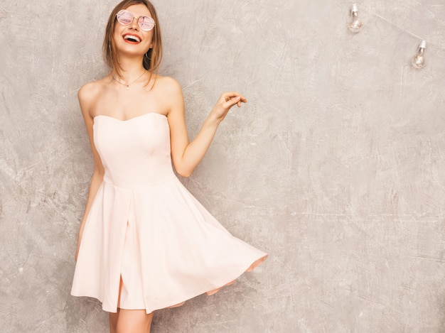 Portrait of young beautiful smiling girl in trendy summer light pink dress. sexy carefree woman posing. positive model having fun. dancing in round sunglasses