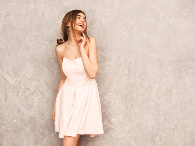 Portrait of young beautiful smiling girl in trendy summer light pink dress. sexy carefree woman posing. positive model having fun. thinking