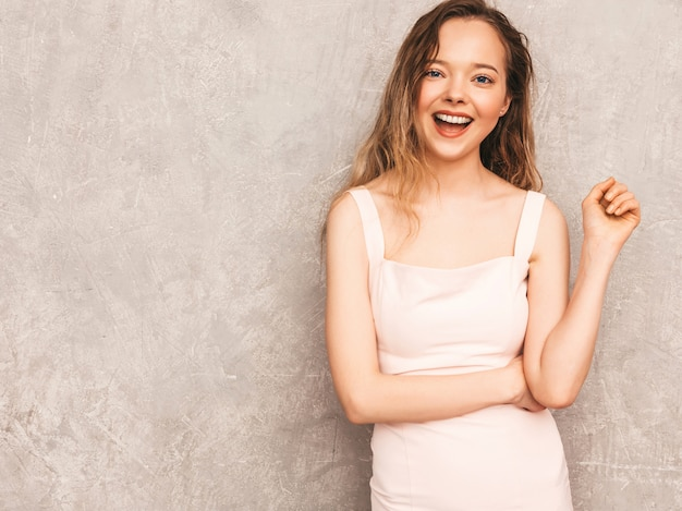 Portrait of young beautiful smiling girl in trendy summer light pink dress. sexy carefree woman posing. positive model having fun