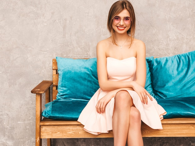 Portrait of young beautiful smiling girl in trendy summer light pink dress. sexy carefree woman sitting on bright blue sofa. posing in luxury interior