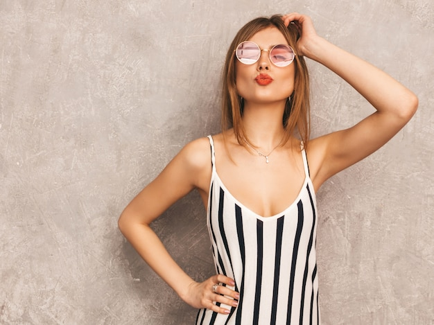 Portrait of young beautiful smiling girl in trendy summer zebra dress. sexy carefree woman posing. positive model having fun in round sunglasses. giving kiss