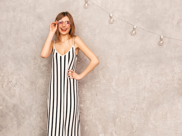 Portrait of young beautiful smiling girl in trendy summer zebra dress. sexy carefree woman posing. positive model having fun in round sunglasses