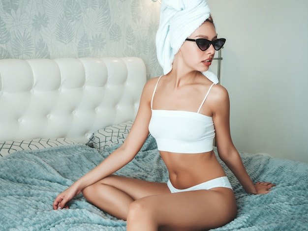 Portrait of young beautiful smiling girl in white lingerie and towel on head