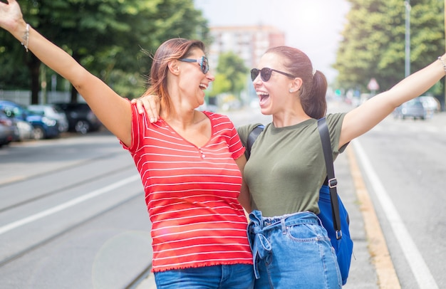 Portrait of young beautiful  smiling girls in a summer day whit colored t-shirt clothes and jeans