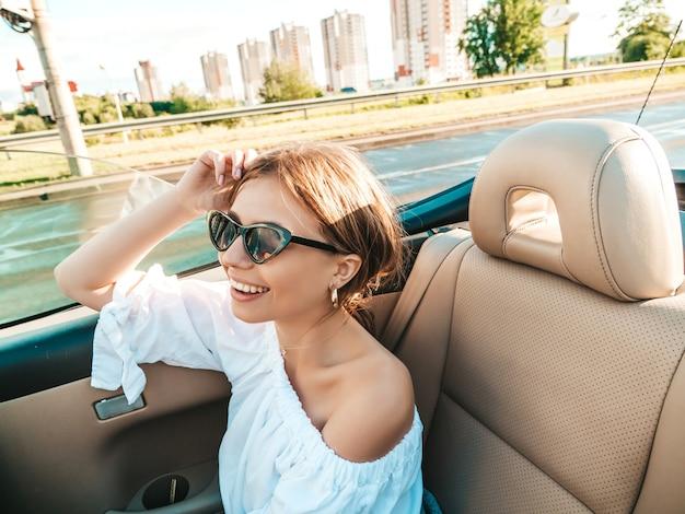 Ritratto di giovane donna hipster bella e sorridente in auto decappottabile