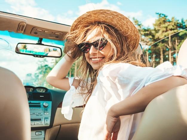 Ritratto di giovane bella e sorridente ragazza hipster in auto decappottabile