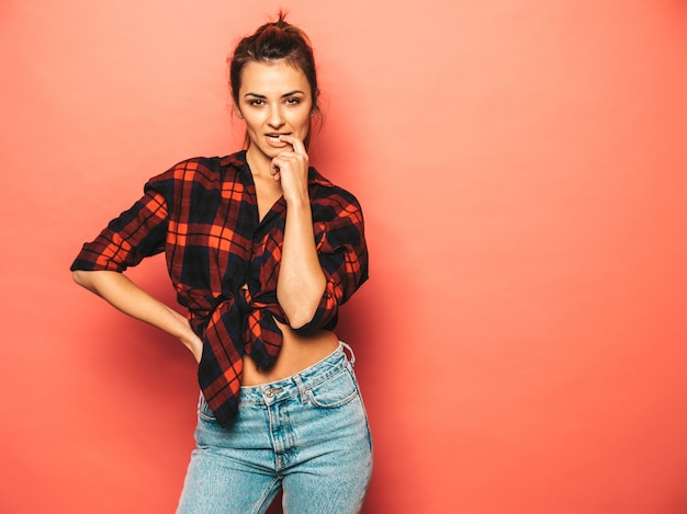 Portrait of young beautiful smiling hipster girl in trendy summer checkered shirt and jeans clothes. sexy carefree woman posing near pink wall in studio. positive model with no makeup