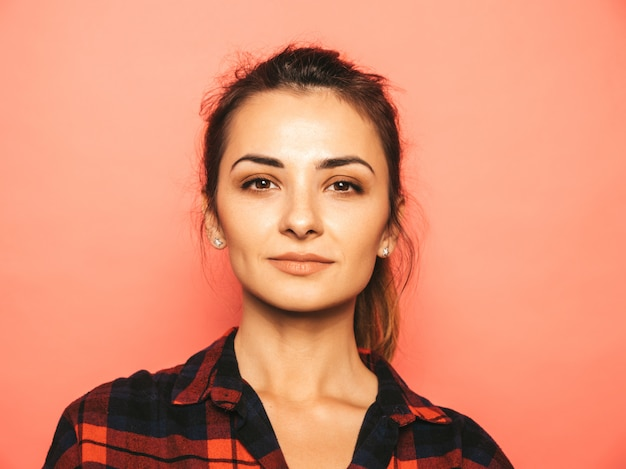 Portrait of young beautiful smiling hipster girl in trendy summer checkered shirt and jeans clothes
