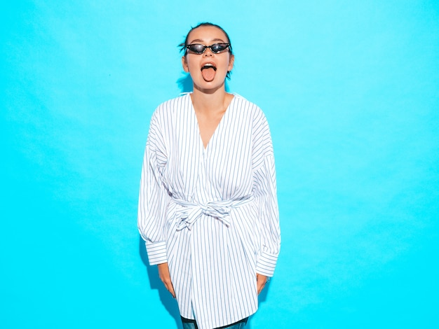 Portrait of young beautiful smiling hipster girl in trendy summer clothes. sexy carefree woman posing near blue wall. positive model having fun in sunglasses.shows tongue