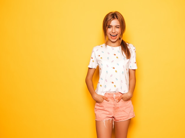 Portrait of young beautiful smiling hipster girl in trendy summer jeans shorts clothes. sexy carefree woman posing near yellow wall. positive model having fun.winking