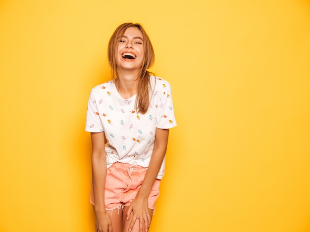 Portrait of young beautiful smiling hipster girl in trendy summer jeans shorts clothes. sexy carefree woman posing near yellow wall. positive model having fun