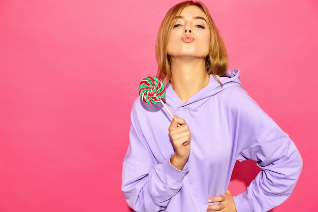 Portrait of young beautiful smiling hipster woman in trendy summer hoodie. sexy carefree woman posing near pink wall. positive model with lollipop, giving kiss