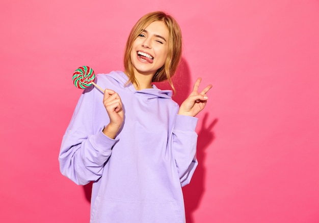 Portrait of young beautiful smiling hipster woman in trendy summer hoodie. sexy carefree woman posing near pink wall. positive model with lollipop winking