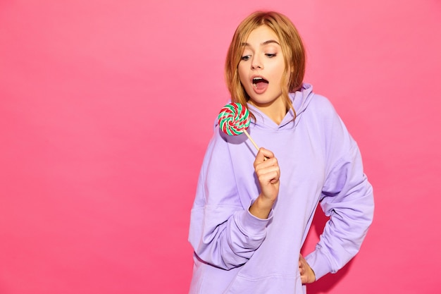 Portrait of young beautiful smiling hipster woman in trendy summer hoodie. sexy carefree woman posing near pink wall. positive model with lollipop