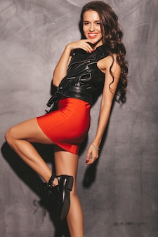 Portrait of young beautiful smiling hipster woman in trendy summer red skirt and black leather jacket. sexy carefree woman posing near wall. brunette model with makeup and hairstyle