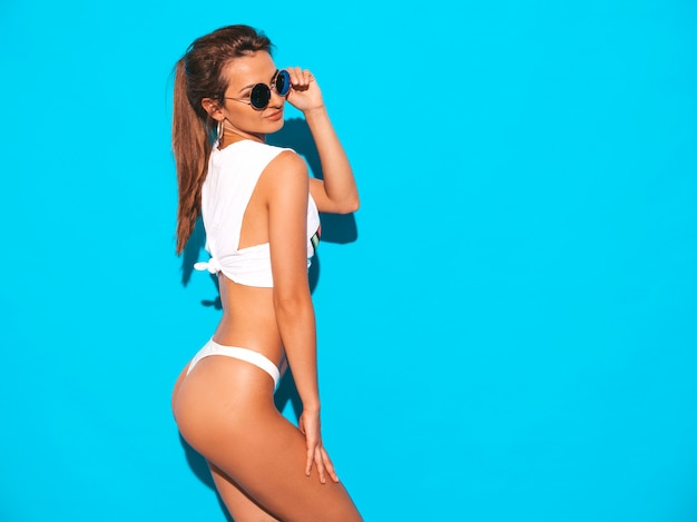 Portrait of young beautiful smiling sexy woman in white summer underpants and topic. trendy girl in sunglasses. positive female going crazy. funny model isolated