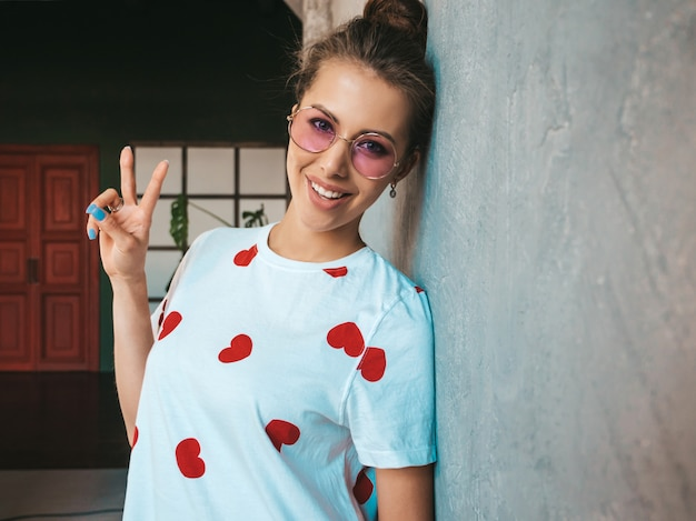 Portrait of young beautiful smiling woman looking at camera  trendy girl in casual summer white t-shirt   shows peace sign