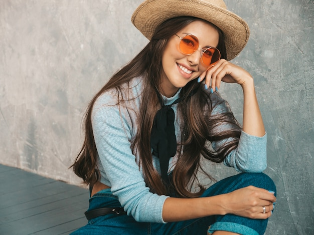 Portrait of young beautiful smiling woman looking . trendy girl in casual summer clothes and hat.  in sunglasses. sitting on the floor