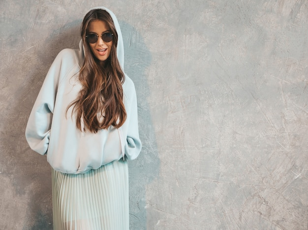 Portrait of young beautiful smiling woman looking . trendy girl in casual summer hoodie and skirt clothes.
