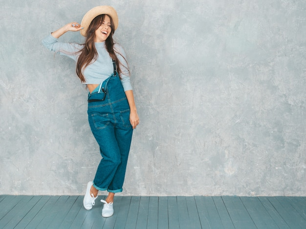 Portrait of young beautiful smiling woman looking . trendy girl in casual summer overalls clothes and hat.