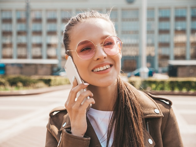 Portrait of young beautiful smiling woman speaking on phone  trendy girl in casual summer clothes  funny and positive female posing on the street