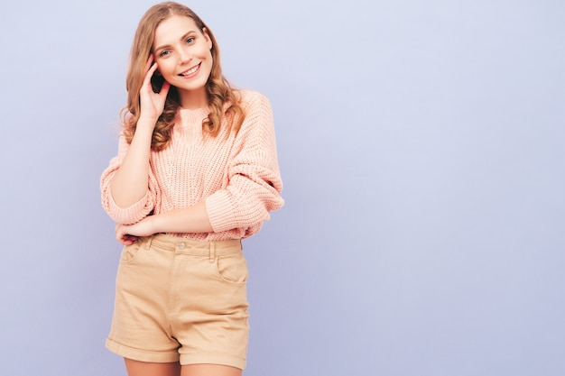 Portrait of young beautiful smiling woman in trendy summer clothes