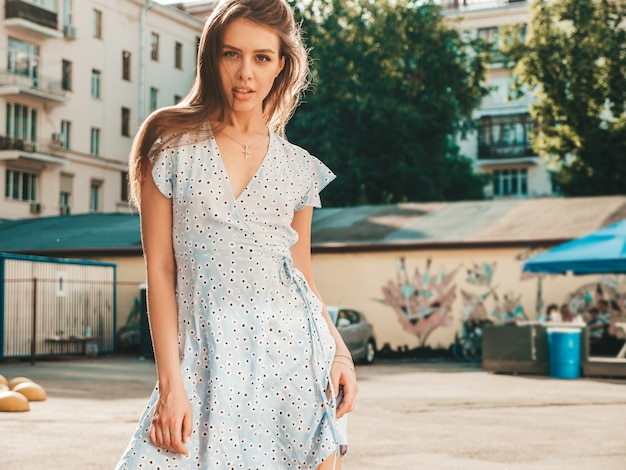 Portrait of young beautiful smiling  woman in trendy summer sundress