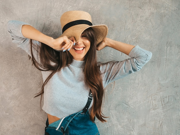 Portrait of young beautiful smiling woman with closed eyes. trendy girl in casual summer overalls clothes and hat.