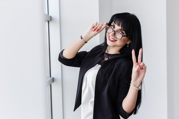 Portrait of young beautiful smiling woman with glasses standing near the window, looking at camera, showing sign victory.
