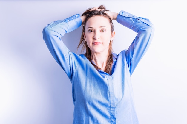 Портрет молодой красивой улыбающейся женщины с руками на голове, хватаясь за волосы.