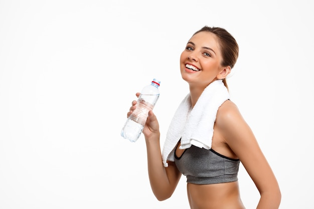 Portrait of young beautiful sportive girl over white background. drinking water