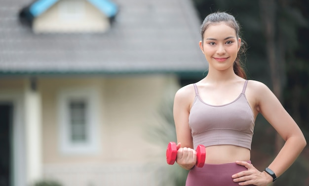 Portrait of young beautiful sportswoman holding red dumbbell, smiling and looking at camera while standing outdoors in front of the house.