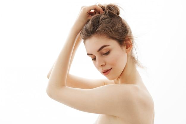 Ritratto di giovane bella donna nuda tenera con il panino che posa nel profilo sopra fondo bianco.
