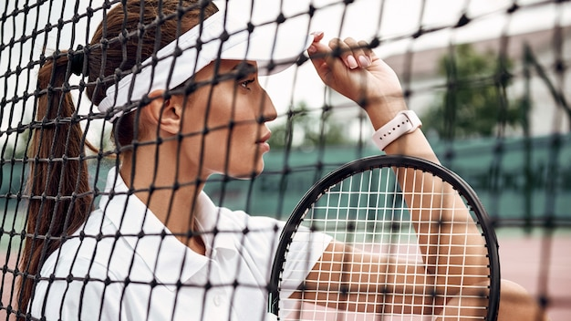 Portrait of young beautiful tennis player with a racket on a court