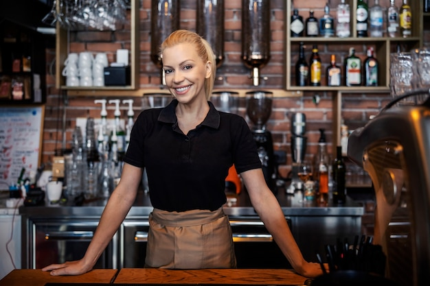 Portrait of a young beautiful waitress in a modern uniform standing with a smile in a cafe leaning against the counter