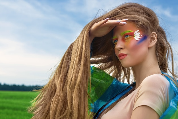 Portrait of a young, beautiful, white, woman with long hair and creative art make-up, close-up in a bodysuit and a raincoat, a green field and a blue sky.