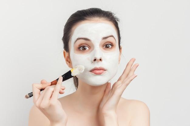 Портрет молодой красивой женщины, применяя маску для лица с кистью чистой кожи